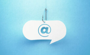 A white speech bubble containing an @ suspended on a fish hook, symbolizing phishing and email scams.