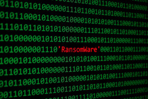 The word ransomware in red in the middle of a screen full of green binary.